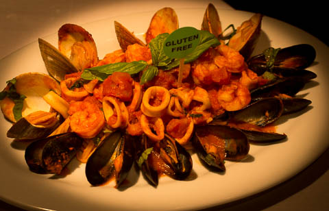 Aqua Pazza spaghetti with mussels, littleneck clams, calamari, and shrimp in a filetto sauce topped with fresh basil